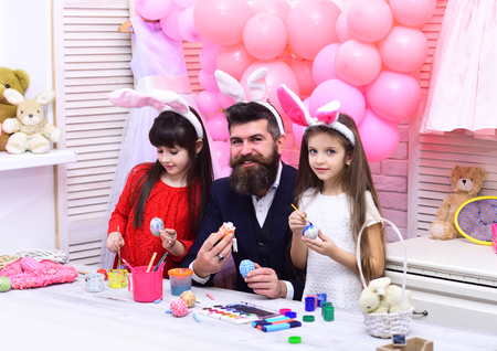 Happy family celebrate spring holiday, love. Easter, father and children in pink bunny ears. Father and daughters paint handmade egg. Happy easter family paint eggs. Family values, childhood, art.