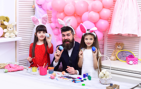 Happy family celebrate spring holiday, love. Happy easter family paint eggs. Father and daughters paint handmade egg. Family values, childhood, art. Easter, father and children in pink bunny ears.