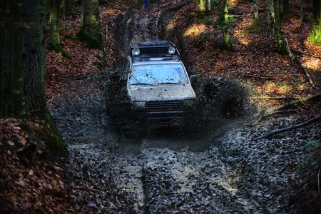 SUV covered with mud stuck in dirt on path covered with leaves. Dirty offroad car with fall forest on background on sunny day. Driving through puddle with splash of mud. 4x4 racing concept.