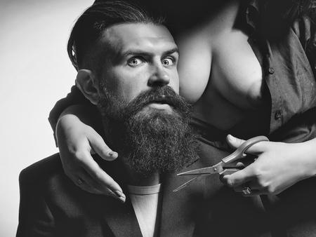 bare woman cutting male beard