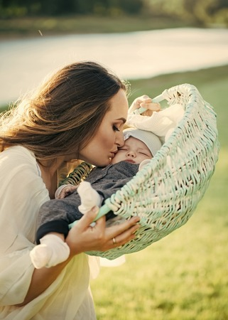 mothers love. Mother woman kiss baby son in basket on natural landscape