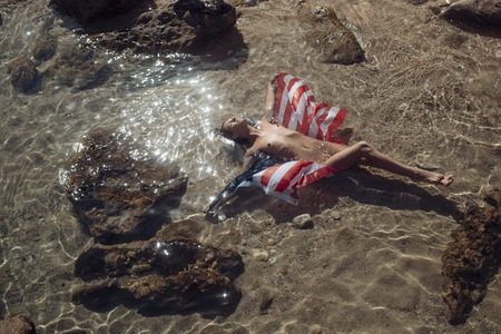 Sensual nude attractive girl on pensive face with usa flag on sunny day. Sexy naked lady lays in water near stone or reef in sea. Woman enjoy sun and suntanning. Vacation and freedom concept