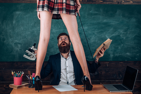 Teacher and student - love story. Sexy education. Bearded sexology teacher looks at two sexy female students. Erotic education and sex Symbols on chalkboard. Lets Talk Sex.
