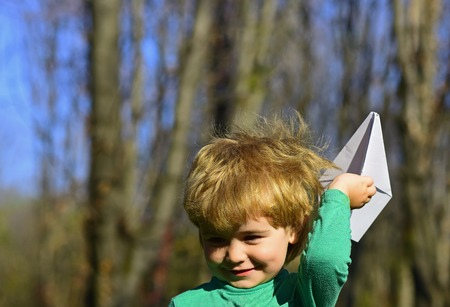 Child play with paper plane toy outdoor. Little child dream of flight. On the waves of my imagination.
