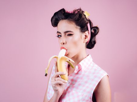 pretty girl in vintage style. pinup girl with fashion hair. banana dieting. pin up woman with trendy makeup. retro woman eating banana. feeling flirty.