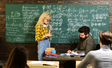 Teachers know about things that make students curious. Final exam test in university students study for examination in classroom. University studying friends studying and reading a books in classroom