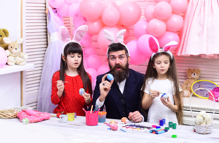 Easter, father and children in pink bunny ears. Family values, childhood, art. Happy easter family paint eggs. Happy family celebrate spring holiday, love. Father and daughters paint handmade egg.