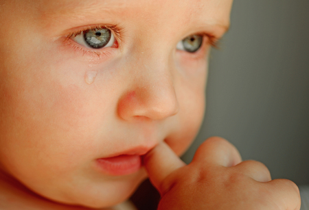 Feeling weepy. Baby with tear rolling down his cheek. Little boy child with sad face. Little baby crying. He is a cry baby