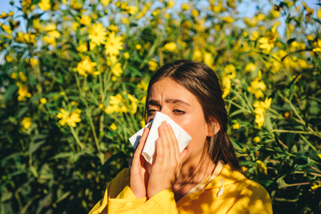 Sneezing young girl with nose wiper among blooming flowers in park. Young woman got nose allergy, flu sneezing nose. The girl suffers from pollen allergy during flowering and uses napkins. Allergy.