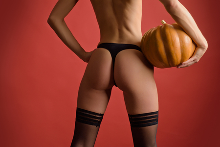 Foto de Sexy buttock. Autumn time for Fashion sale. Happy Halloween Sexy Witchs with Big sexy ass. Night Party background. Copy space for text. Pumpkin with sexy ass. Woman shows a beautiful ass or butt. - Imagen libre de derechos