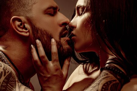 Photo pour Kiss. Close up portrait of couple in love is kissing. Real romantic passionate moment. Bearded man with tattoo clasping beautiful girlfriend. Emotive of sexy couple. - image libre de droit