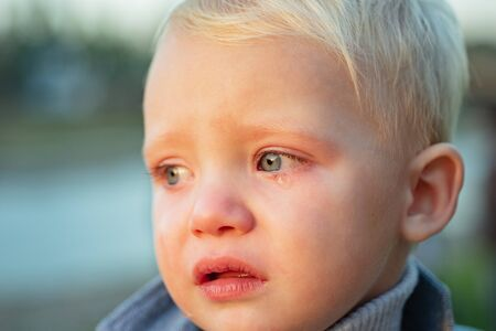 Little boy with tears close up defocused background. Emotional sad baby. Toddler sad face crying. Sad emotions. Hard to be toddler. Cute son crying face. Reasons baby crying. Tears on eyes