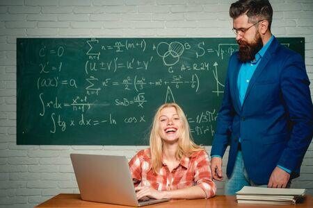 Teacher teaches a student. School day. Science and education concept. Teacher and student sit together at education class. Teachers day. Bearded tutor helping his student.