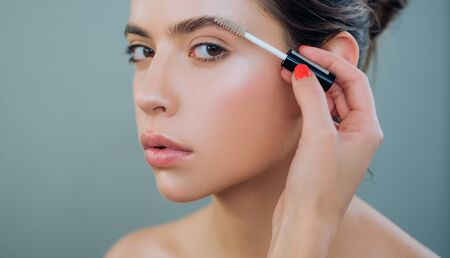 Photo pour Care beauty eyebrow. Beautiful woman with brow brush in hand. Attractive sexy girl with glamorous professional nude makeup brushing up her perfect eyebrows with brush. Natural eyebrow makeup look. - image libre de droit