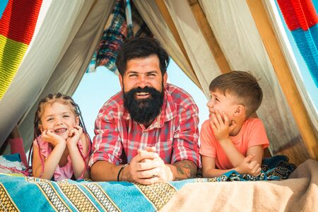 Photo for Young hipster bearded dad play with his children at colorful playhouse at the roof. Father have fun with his cute daughter and son. Happy family enjoy being together and play. - Royalty Free Image