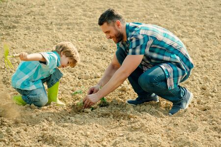 Photo pour Father and son work on earth ground. Family planting. Daddy teaching little boy to do gardening. - image libre de droit