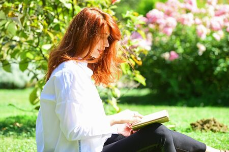Photo for Student girl reading a book in park and sitting on grass. Redhead woman Sitting in grass with book in spring garden. Woman enjoying literature indoor in spring park. - Royalty Free Image