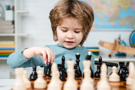 Foto de Kid Playing Chess. Kids educational games, child early development. Clever concentrated and thinking child while playing chess. - Imagen libre de derechos