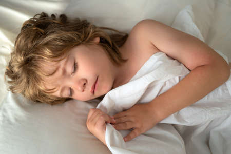 Photo pour Sleeping kids lies in bed with eyes closed. - image libre de droit