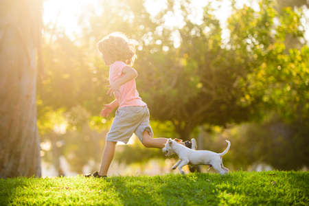 Photo for Boy child walk with puppy. Kid with pets running. Happy Child and dog runs at backyard lawn. - Royalty Free Image