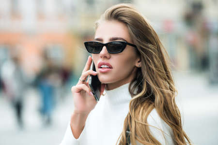 Photo for Beautiful and sexy elegant young woman using her smartphone. Street portrait. Seductive young woman. High fashion female model. - Royalty Free Image