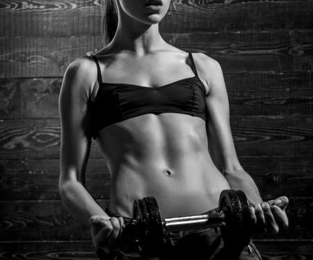Photo for girl gym dumbbells. Fitness model doing intense training. Woman working out with dumbbells on dark wooden background. Girl lifting the dumbbells. Fitness woman. - Royalty Free Image