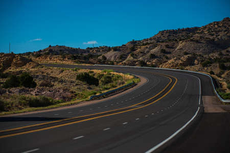 Asphalt highway and hill landscape under the blue sky. Road in America.
