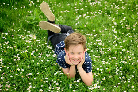 Photo for Unity with nature concept. Child lying on grass background. Cute kid boy enjoying on field and dreaming. - Royalty Free Image