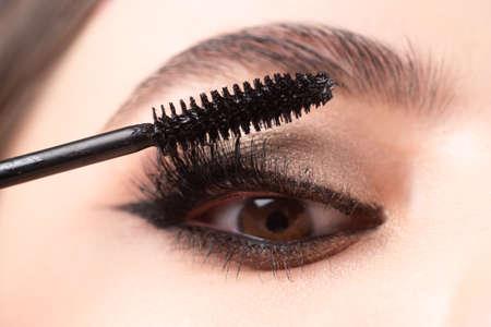 Photo for Closeup of eye makeup. Applying maskara on lushes Young woman getting make up with brush. Eyes visage woman. - Royalty Free Image