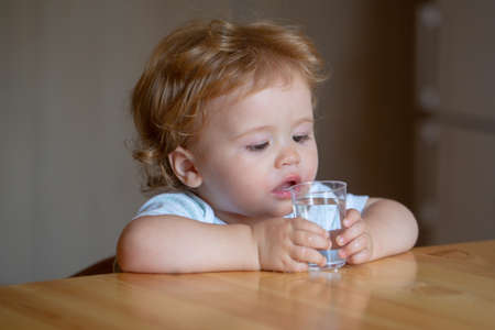Photo for Healthy nutrition for kids. Baby drink water. Portrait of a sweet Beautiful child drinking a glass of water. - Royalty Free Image