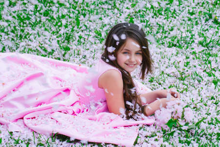 Photo for Beautiful little girl in pink dress with smiling happy face lying on green grass covered with spring flower blossom petals outdoor. - Royalty Free Image