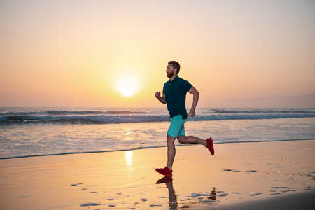 Photo pour Full length of healthy man running and sprinting outdoors. Male runner. Man running on the beach at sunset. Healthy lifestyle concept. - image libre de droit