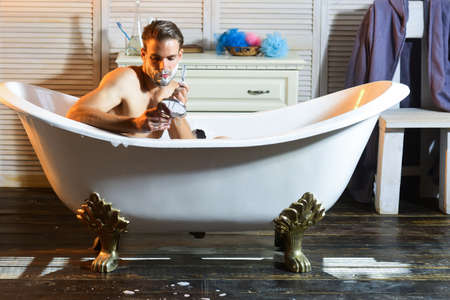 Photo pour Shaving man. Guy shave with razor in bath in bathroom. Macho with shaving soap on beard hair look in mirror - image libre de droit