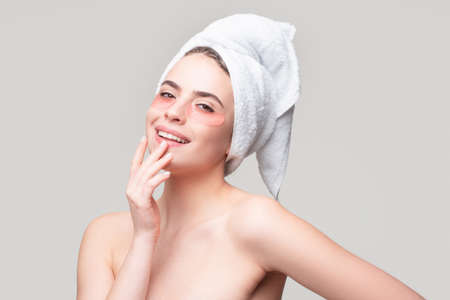 Photo pour Close up portrait of sensual girl with towel on head and eye patches. Eyes mask cosmetic patches woman face closeup. - image libre de droit