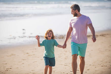 Photo pour Father and son walking on summer beach. Dad and child boy holding hands and walk together. Family travel, vacation, fathers day concept. - image libre de droit