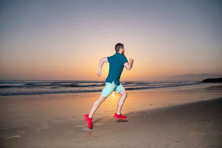 Photo for Man running on the beach at sunset. Man runner jogger running. - Royalty Free Image
