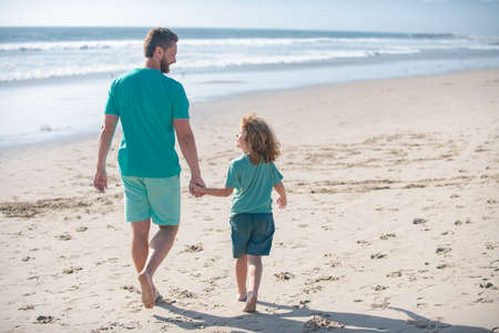 Photo for Dad and child boy holding hands and walk together. Father and son walking on summer beach. Concept of friendly family and of summer vacation. - Royalty Free Image