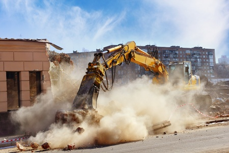 Bulldozer crushing the building at construction site