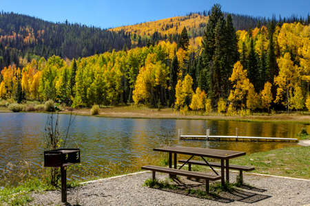 Picnic area on shore of mountain lake on warm fall afternoon with brightly colored trees changing color reflecting on water surface