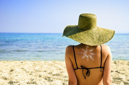 Photo for Woman on beach with sun symbol on her back - UV protection concept - Royalty Free Image