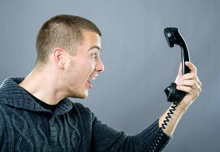 Upset young man with funny facial expression yelling on phone
