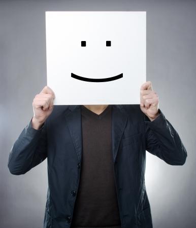 Studio shot of man behind smiley symbol
