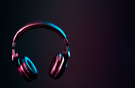 Headphones with pink & blue colored lighting, futuristic lifestyle/music image with copy space.