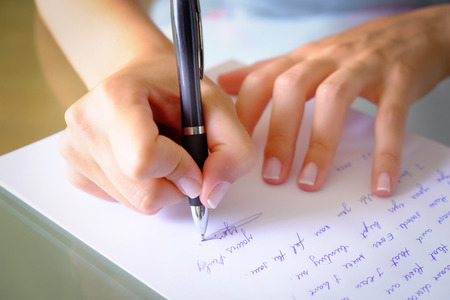 writing a letter with a black pen