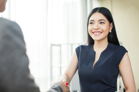 Foto de Beautiful Asian businesswoman smiling and shaking hands with other businessman - Imagen libre de derechos