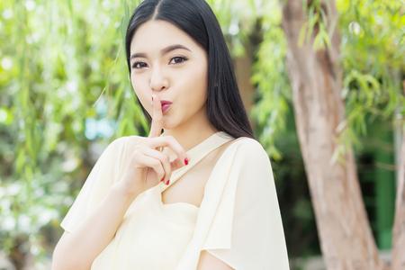 Foto de Beautiful Asian woman with her top secret gesture - Imagen libre de derechos