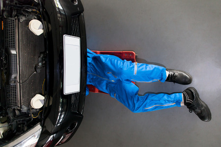 Photo pour Mechanic in blue uniform lying down and working under car at the garage. - image libre de droit