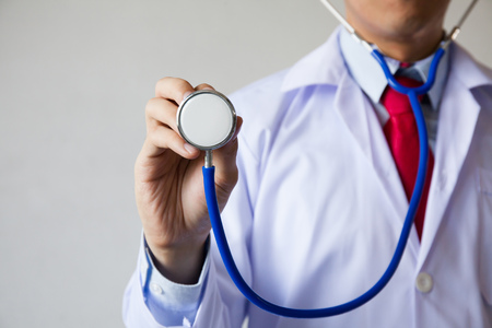 Foto de Close-up of male doctor using stethoscope and focusing on stethoscope - Imagen libre de derechos