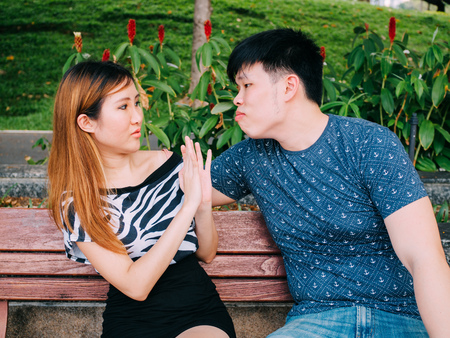 Young Asian man trying to kiss a girl and gets rejected