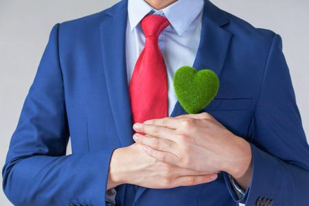 Photo for Businessman in suit holding a green heart shape - white background - indicates eco-friendly , social and environmental responsibility business concept - Royalty Free Image